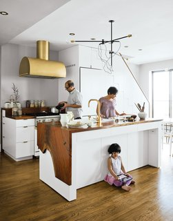 Let There Be Light: 4 Types of Kitchen Illumination - Photo 4 of 4 - The Mandayam–Vohra family gathers under one of Workstead's signature three-arm chandeliers, shown here in its horizontal configuration.