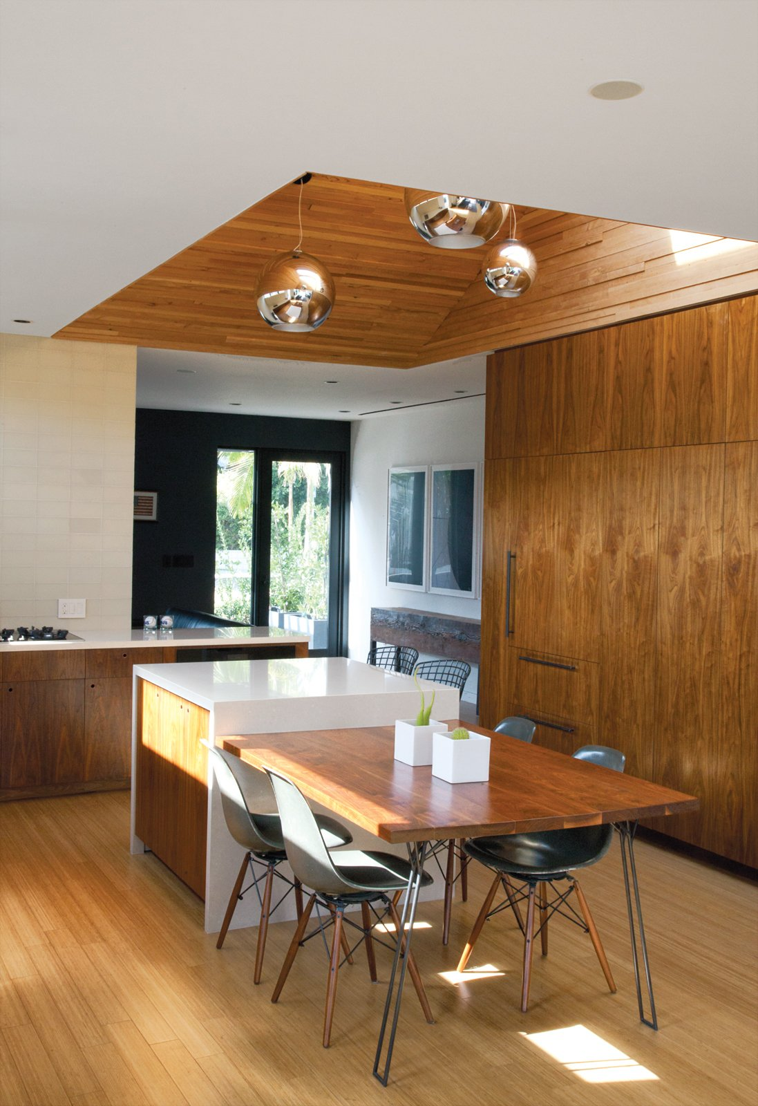 "Bill Thompson's Hollywood home exudes modern cool with a custom walnut dining table and chairs from Modernica. Tagged: Kitchen, Pendant Lighting, Wood Cabinet, and Cooktops.  Photo 1 of 9 in You Won't Be Calling This House a ""Man Cave"""
