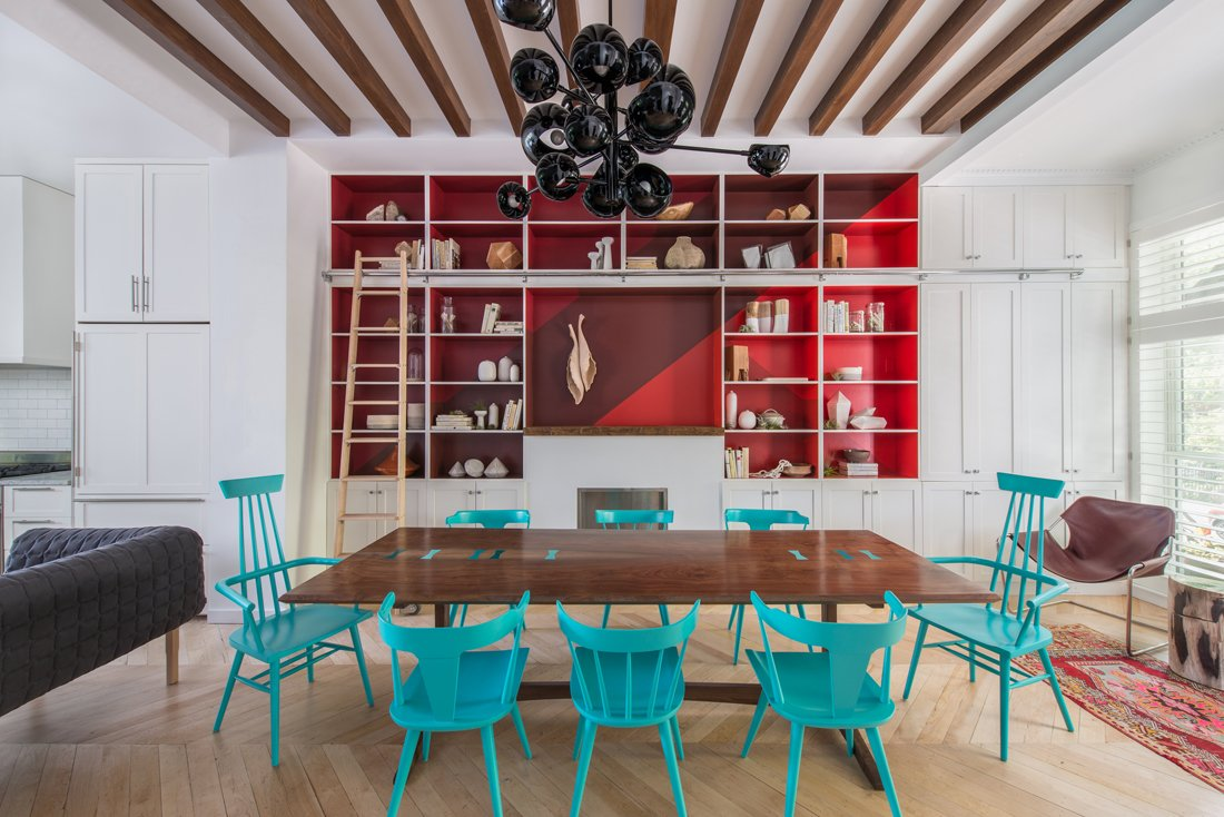 A quartet of red paints (Raspberry Truffle, Million Dollar Red, Vermillion, Arroyo Red), all by Benjamin Moore, make the built-in shelving in the dining area pop. The table is a custom design made of bookmatched walnut slabs joined by lacquered butterflies. The chairs are vintage Paul McCobb lacquered in turquoise (Benjamin Moore's Aruba Blue). The Ligne Roset Ruché sofa, designed by Inga Sempé, separates the living and dining spaces. The chandelier is by David Weeks Studio.  Color Splash by Kelsey Keith from Material Focus: Custom Walnut Designs