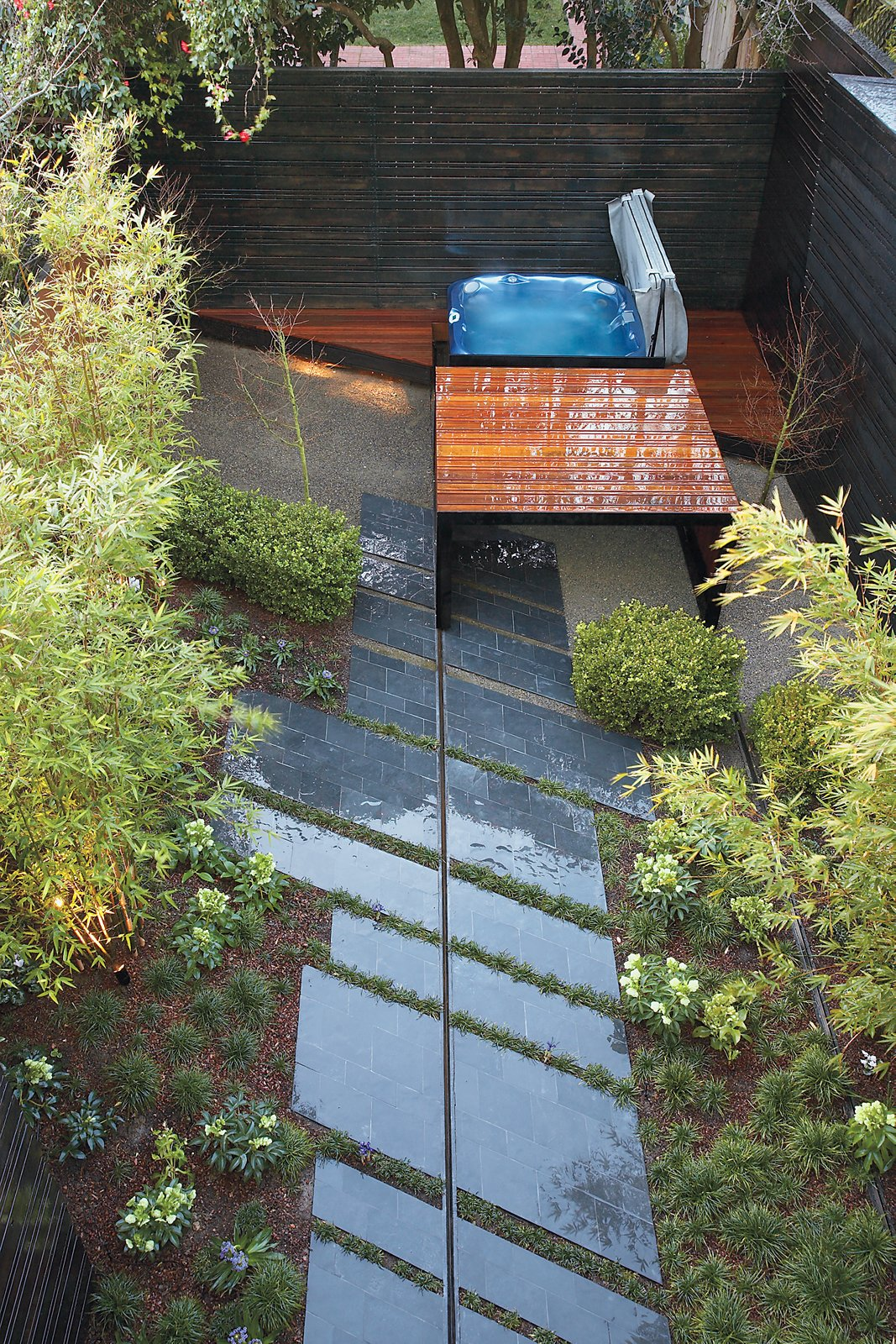 Parallelogram-shaped stone slabs line the walkway to the hot tub.