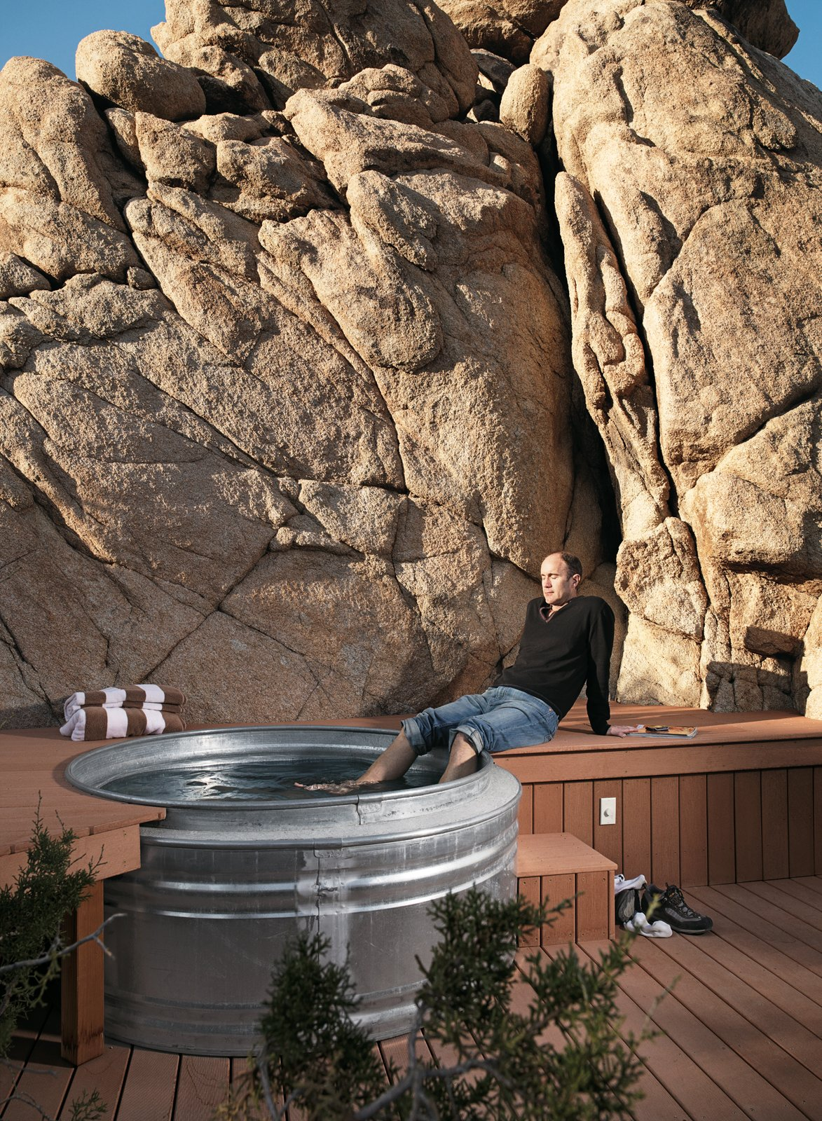 "Nighttime hikes often end at the the ""cowboy"" hot tub where Smith soaks his feet: two nested Hastings galvanized livestock feeders. The tub is surrounded by a Veranda faux-wood deck and fed with hot water from the house's solar hot-water system.  Tubs by Jenny Xie from Small ""Hybrid Prefab"" Home in the Desert"