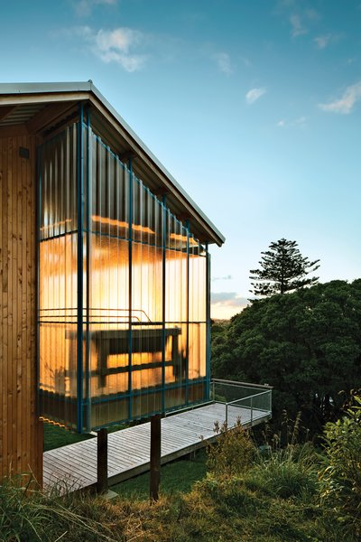 Rookie firm Patch Work Architecture used locally sourced Lawson cypress to clad the exterior of a 970-square-foot house in New Zealand. Vibrant painted accents contrast with the otherwise neutral structure. Steel trusses, painted in a blue hue called Lochmara from Resene, are visible through the fiberglass panels on the veranda. Photo by: Paul McCredie
