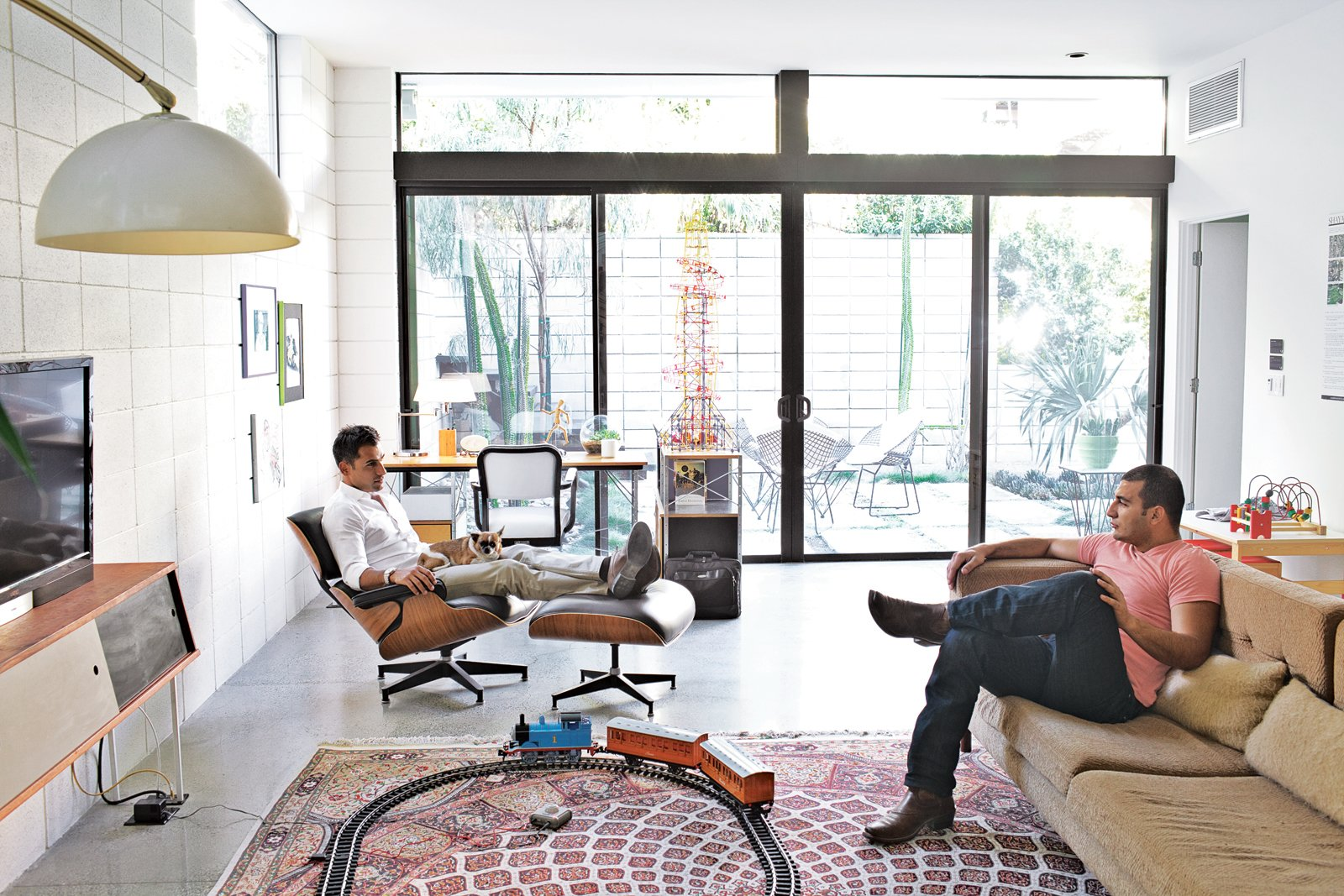 """Brothers Nima and Soheil relax in the family room on an Eames lounge chair and a custom sofa they designed. """"Mid-century architecture draws the outdoor environment indoors,"""" says Soheil. """"There's a lot of natural light, a lot of ventilation."""" Tagged: Living Room, Recliner, Sofa, Floor Lighting, Concrete Floor, Console Tables, Ottomans, Rug Floor, Chair, and Desk.  Midcentury Homes by Dwell from The First LEED Gold-Certified Family Home in San Diego"""