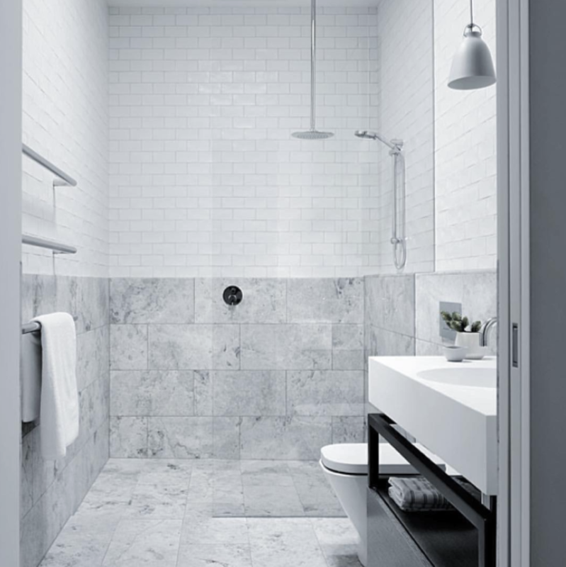 Light gray stone and stainless steel fixtures make up the palette of this clean bathroom.