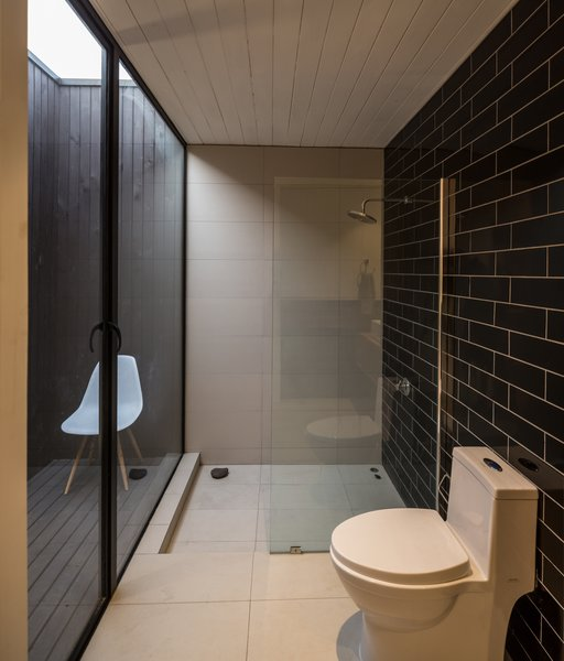 """The water waste from the shower and the kitchen irrigate the interior garden,"" LLaumett says. ""The toilets have their own patio, which provides them with ventilation and natural light."" Black Marazzi tiles cover the wall. Photo 7 of Unplugged modern home"