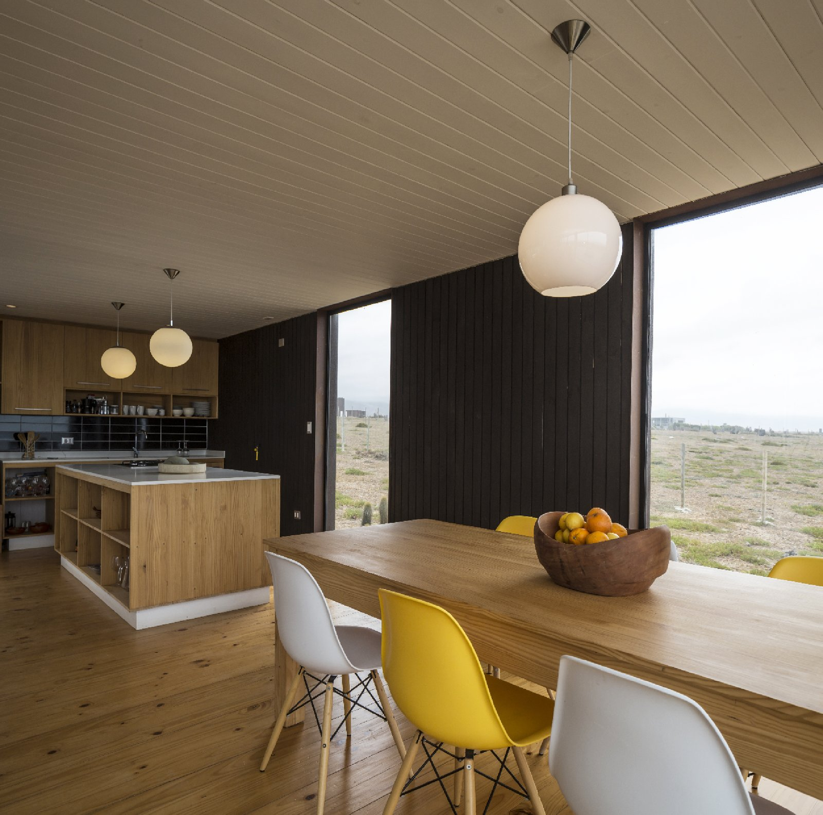 Eames DSW Molded Fiberglass chairs surround the dining table made of local wood and constructed by the owners.  Unplugged by Kelly Dawson