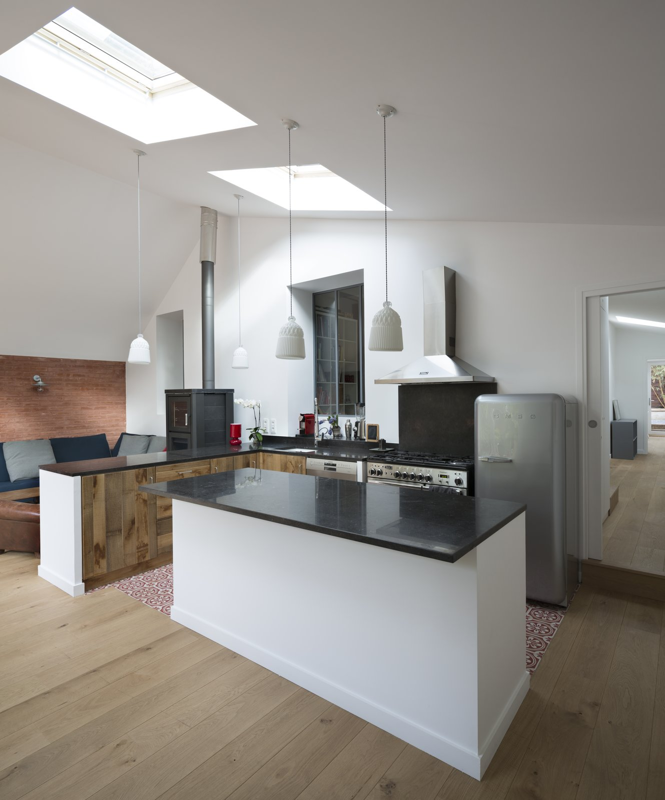 The kitchen features countertops from Pierre Bleue de Hainaut.  Wisteria Residence by Kelly Dawson