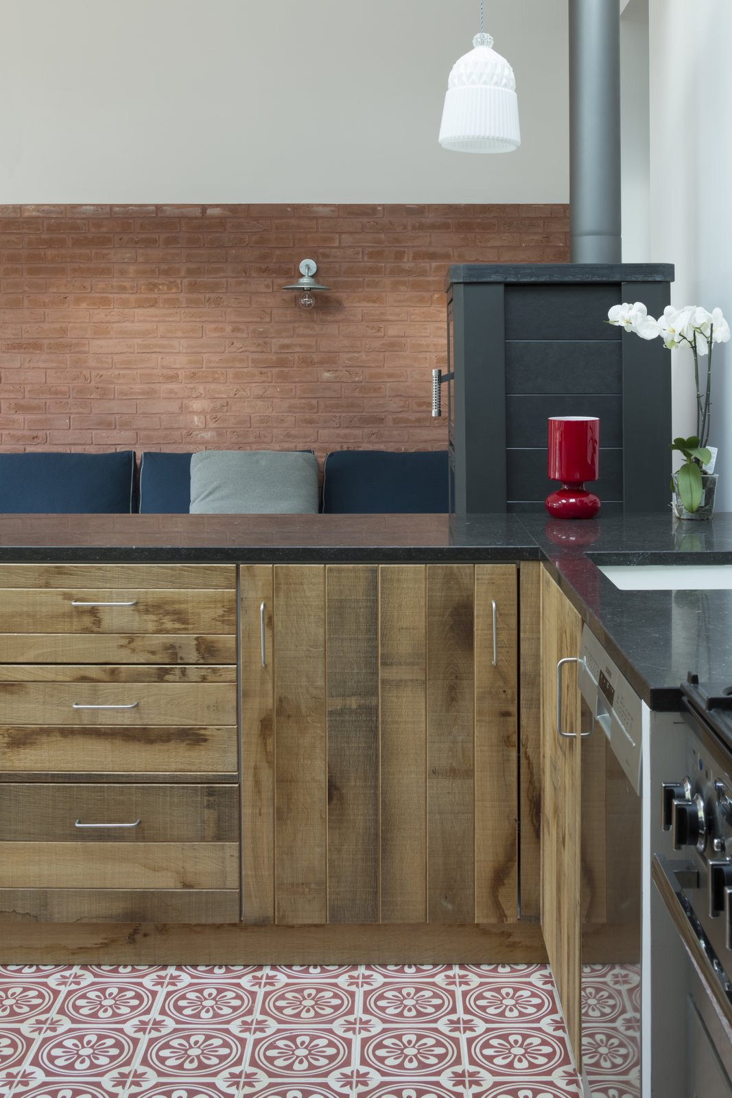 Carocim tiles and custom wood cupboards add lively details to the kitchen's contained space.