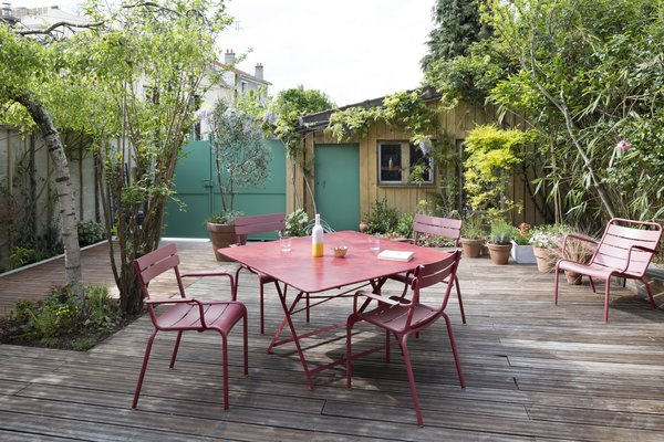 A dining set by Fermob, featuring Luxembourg chairs, makes alfresco meals easy. Photo 8 of Wisteria Residence modern home