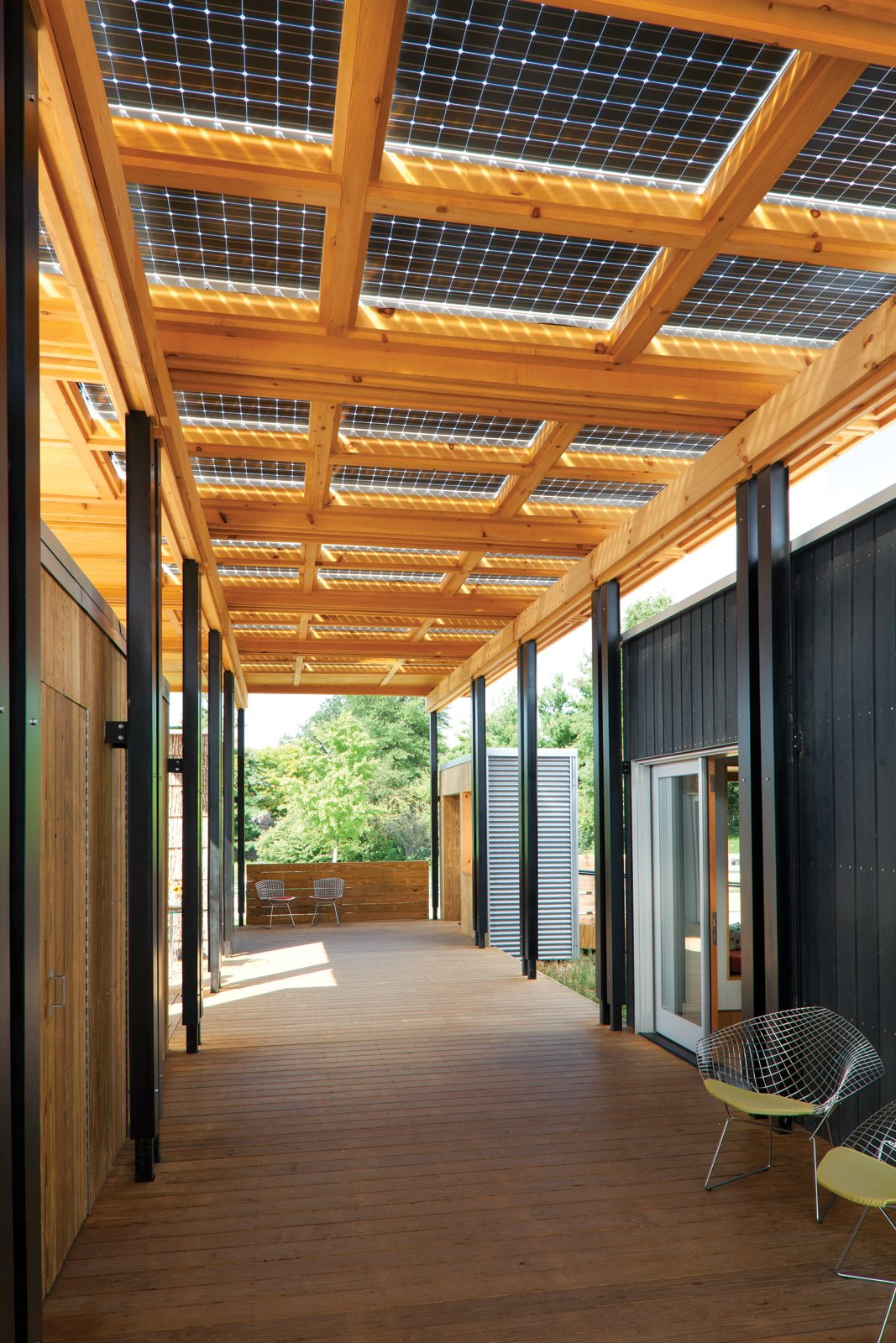 Porches are a beloved element of the Southern vernacular and lifestyle, traditionally serving as an extension of the indoors—a shady place to gather, socialize, or share a meal. So when the students of Appalachian State University in Boone, North Carolina, entered the Solar Decathlon, a biennial energy-efficient residential design competition, the iconic space figured prominently in their concept. Here, a canopy of bifacial solar panels covers the porch and provides energy for the home. Tagged: Outdoor and Wood Patio, Porch, Deck.  12 Porches Across America by Diana Budds from About Face