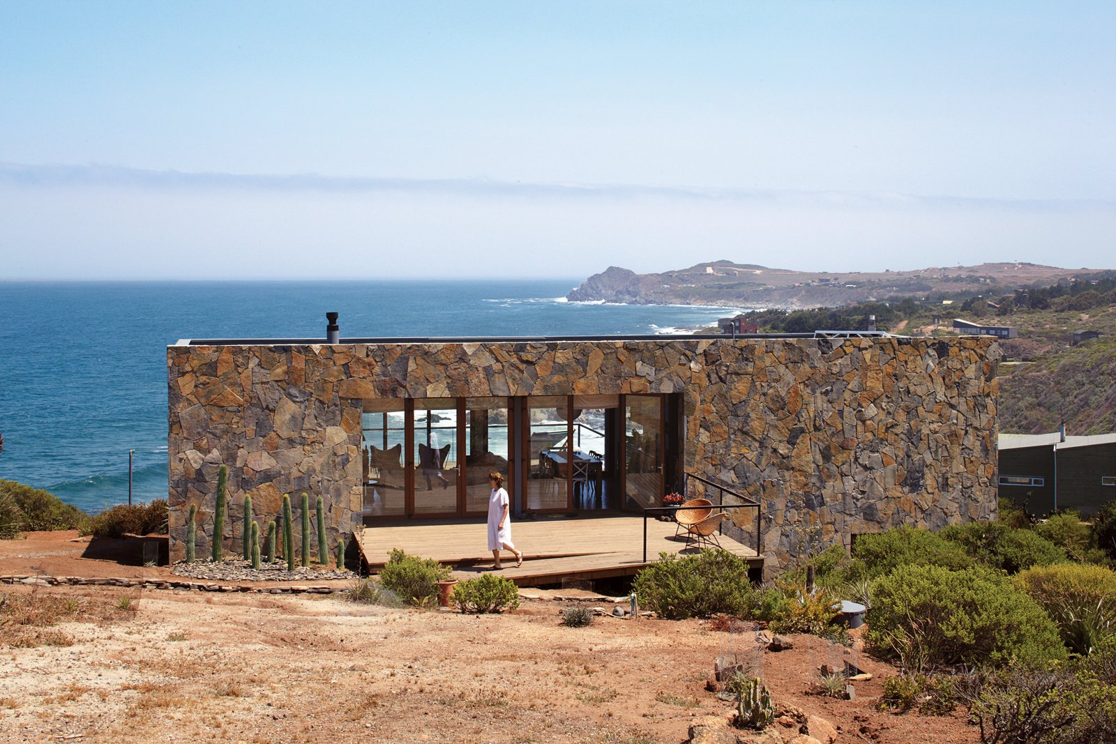 The Casa Cuatro sits above a 180-foot cliff that overlooks the Pacific Ocean. The locally quarried stone makes the house blend in with the landscape and acts as a thermal-mass wall, absorbing heat during the day and releasing it through the evening. Tagged: Shrubs, Back Yard, Exterior, Stone Siding Material, and House.  The Most Popular Homes in Dwell: 81-100 by Diana Budds from Tunquen Treasure