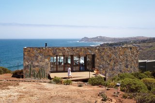 9 Modern Beach Bungalows - Photo 3 of 9 - Dubbed Casa Cuatro, this stone-covered house designed by Barbara Bernal sits above a 180-foot cliff that overlooks the Pacific Ocean. The locally quarried stone makes the house blend in with the landscape and acts as a thermal-mass wall, absorbing heat during the day and releasing it through the evening.