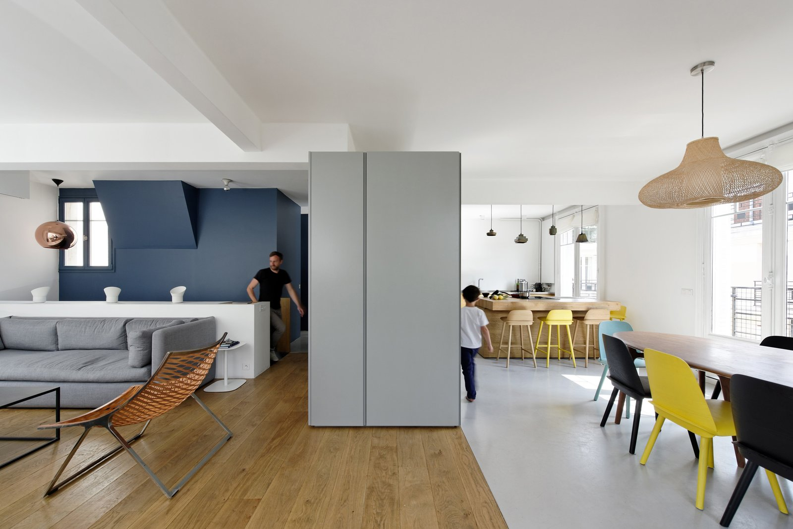 """""""The upper floor includes the entry, cloakroom, guest bathroom, kitchen, dining room, living room, and terrace,"""" Hammer says. """"In contrast to the lower floor and its separated rooms, the living area is composed as an open space with no walls."""" Nerd Chairs by David Geckeler for Muuto surround a handcrafted nutwood table in the dining room."""