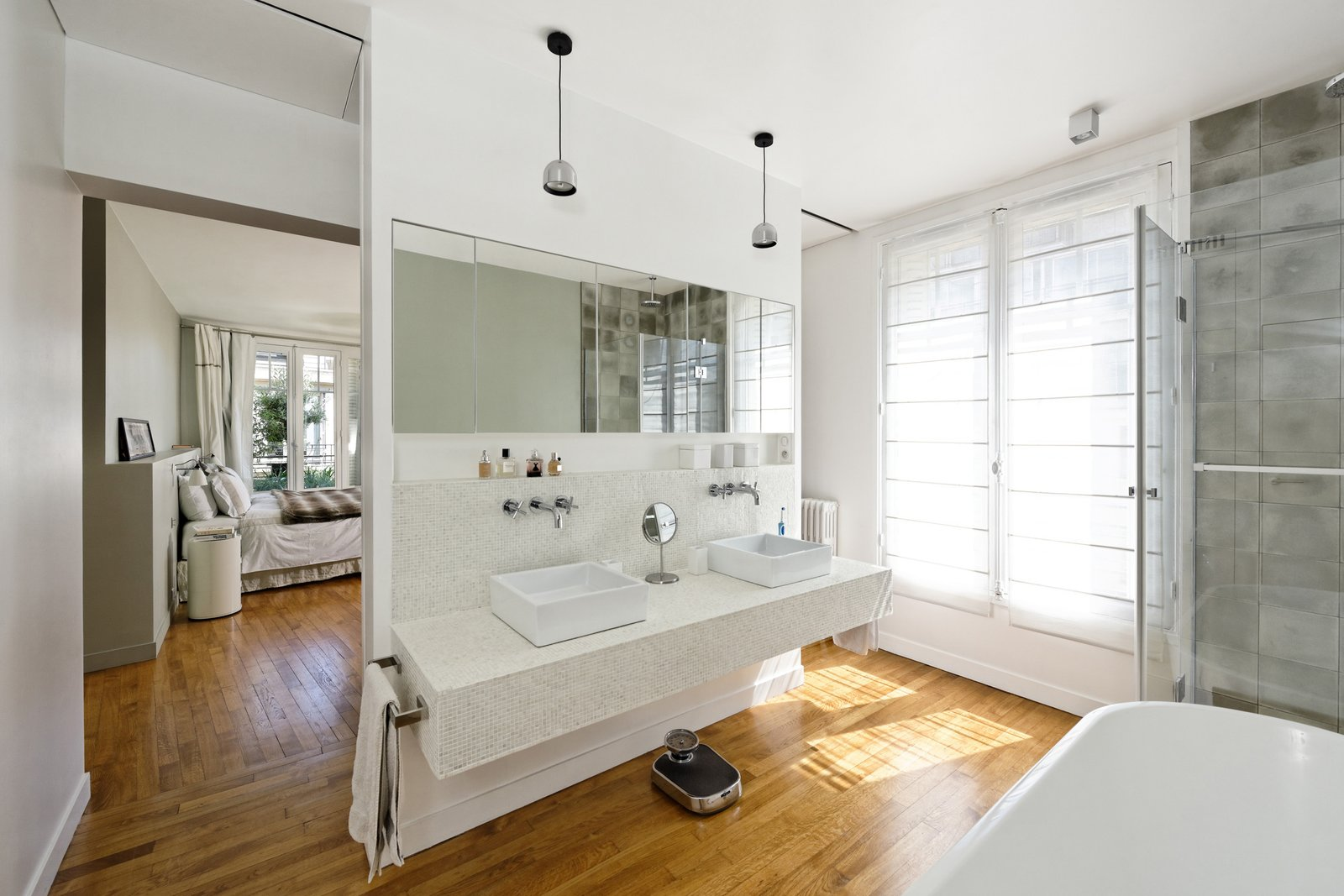 """The old living room and balcony on the sixth floor were transformed into the master bedroom with an en-suite open bathroom,"" Hammer said. Flos lighting illuminates the space above the vanity. 10 Dreamy Parisian Homes - Photo 3 of 11"