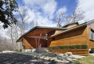 After a Fire, a Midcentury Home Rises from the Ashes - Photo 1 of 7 - The Douglas fir slats cover the facade and are repeated throughout the rest of the house. Moser references the woods by a pair of steel beams on the front porch that allude to the silhouette of a tree.