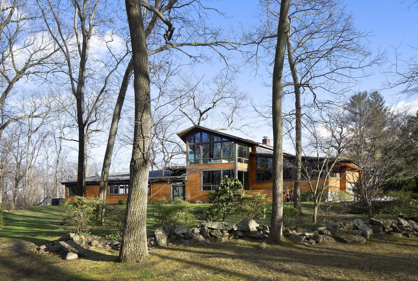 When Moser first arrived on the site, the original home had almost no good views of the neighboring Saxon Woods. The solution was to build expansive Low-E windows to enjoy views of the woods.  Photo 2 of 7 in After a Fire, a Midcentury Home Rises from the Ashes
