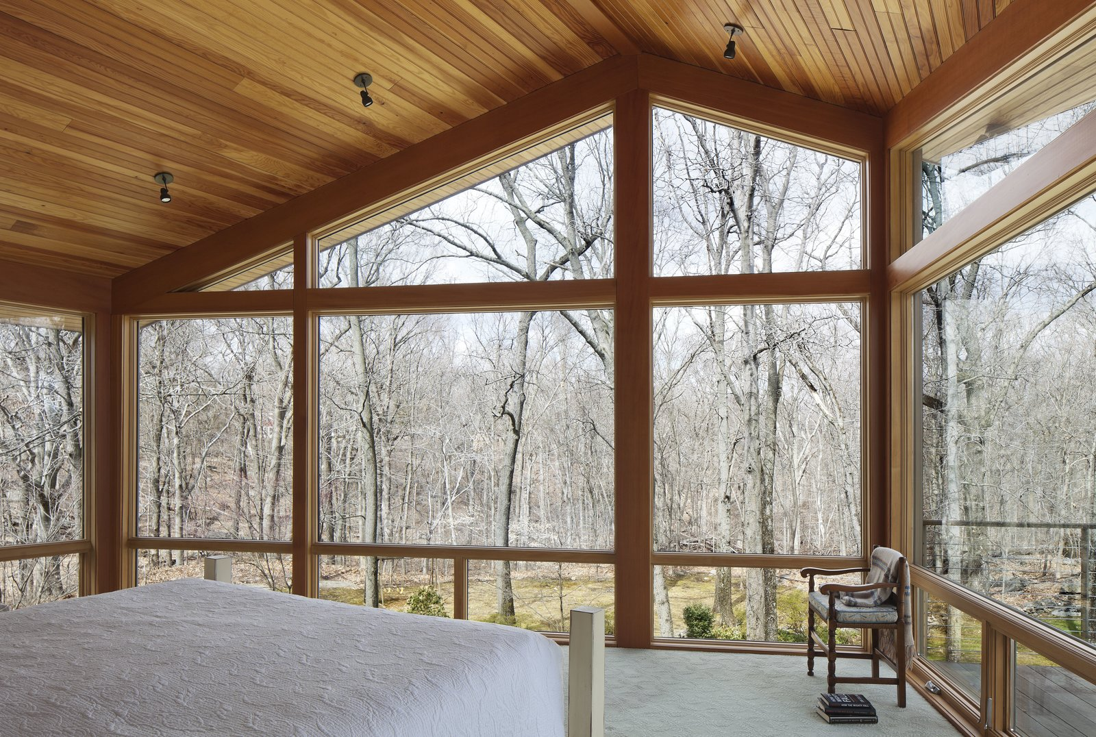 From the northeast corner of the master bedroom, the homeowners can walk out onto a deck area to enjoy the view of the woods.  Bedroom by David Seah from After a Fire, a Midcentury Home Rises from the Ashes