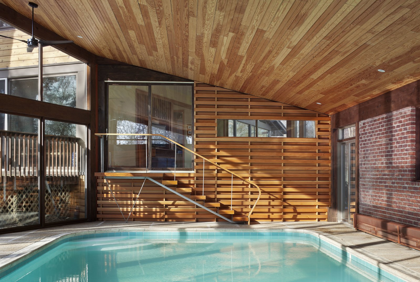 One of the biggest challenges of designing around an indoor pool was managing the humidity, especially with a sloping Douglas fir ceiling. Moser explains that by using a retractable pool cover it helps manage humidity levels. While in the winter there is low humidity, a little actually prevents the wood from drying out.  Photo 5 of 7 in After a Fire, a Midcentury Home Rises from the Ashes