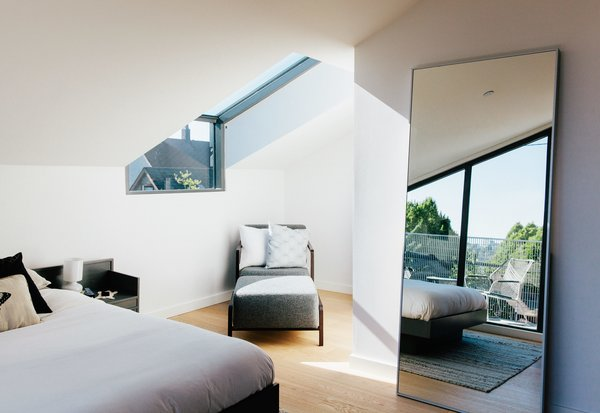 Dick Hellofs and Karli Gillespie occupy a new house at the back of the site. Light streams into their bedroom through a Spectrum Skyworks skylight, shining on an armchair and ottoman from Calligaris, while an IKEA mirror reflects a refurbished 1960s bed.