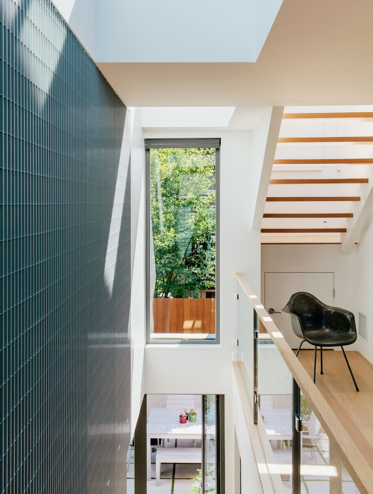 The laneway house features Kentwood engineered-wood floors, Cascadia windows, and aluminum-bar grating. The Eames DAX chair is vintage.