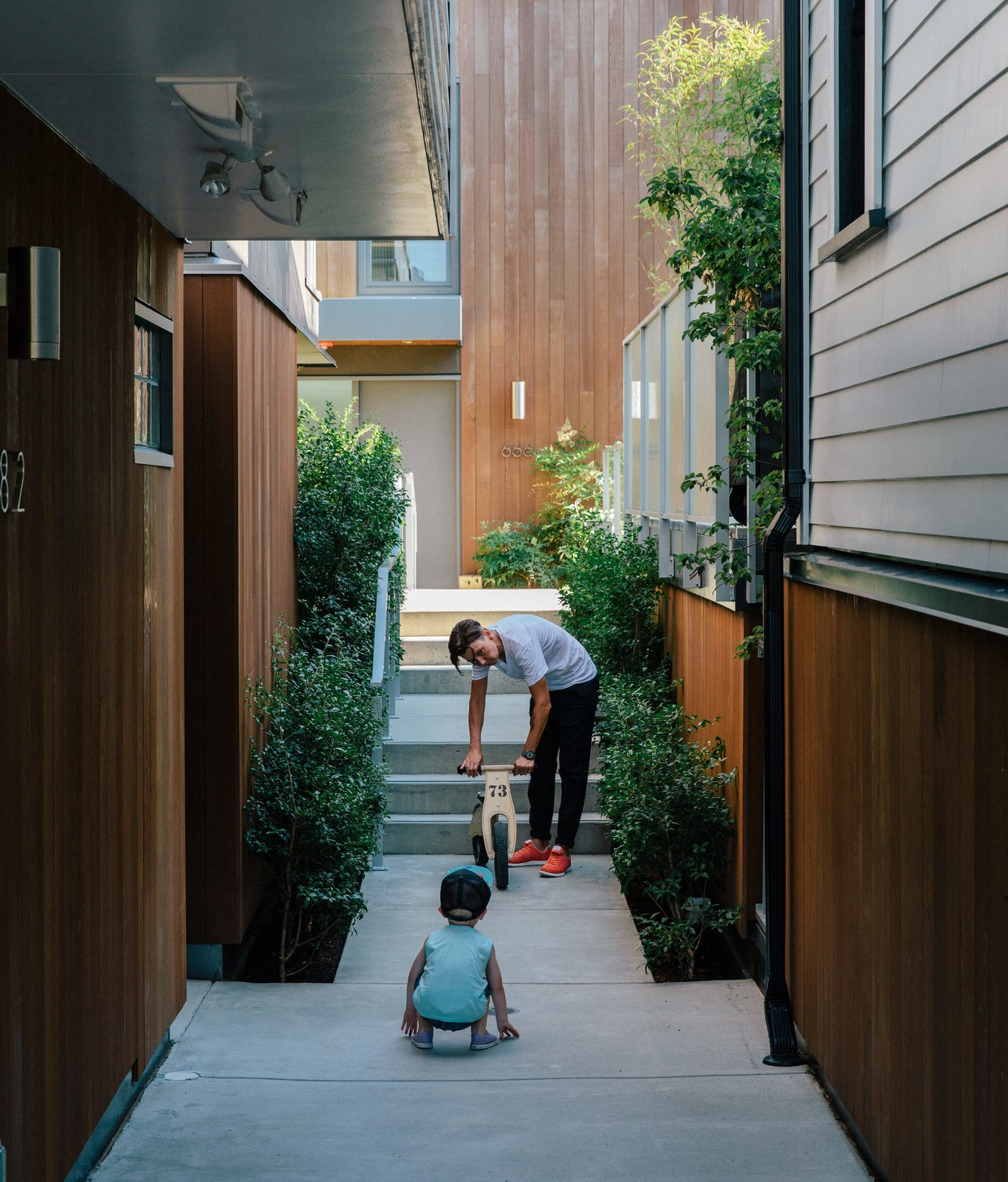 Resident Misha Bukowski plays with young Zachary in the walkway between the renovated buildings. The new units are clad in stained local cedar. Tagged: Outdoor, Small Patio, Porch, Deck, and Concrete Patio, Porch, Deck.  Best Photos from As Housing Costs Soar, Two Homes Multiply to Seven