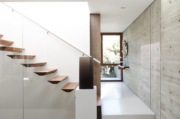 """""""We didn't want panel-formed, smooth-like-glass concrete; we wanted texture,"""" Fleetwood says. A cast-resin piece by DeWain Valentine sits at the foot of the sculpted walnut stairs."""