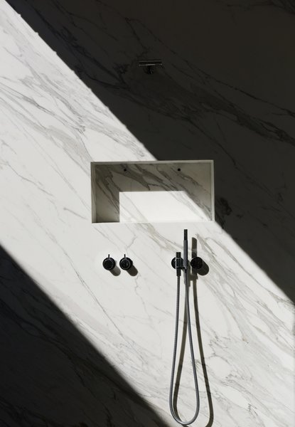 A shaft of sunlight streams into the marble shower, through a glass atrium that connects the master suite to the outdoors while maintaining privacy; the fixtures are by Vola.
