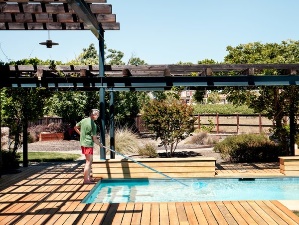 "A level, trellised garapa-wood deck connects the main structure to the pool house. ""The arbors near the pool knit everything together,"" says Mikiten. ""The deck is constructed over a drainage pit so the wood surface can be completely flush with the interior floor and the surrounding yard, which is critical for a fluid experience by someone using a wheelchair."""
