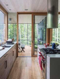 """It Took a Whole Family to Build This House - Photo 6 of 13 - In the kitchen, the cabinetry is walnut veneer with a weathered finish applied by cabinetmaker David Rogers. """"The process involved sanding and rubbing in stain as well as adding a clear finish,"""" project architect Eero Puurunen says."""