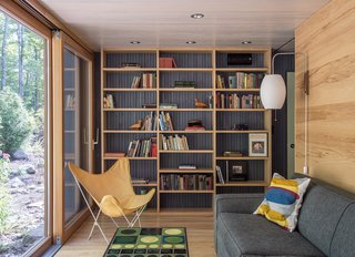 It Took a Whole Family to Build This House - Photo 8 of 13 - In the library, a Grant sleeper sofa by Mitchell Gold + Bob Williams is paired with a Cigar wall sconce by George Nelson.
