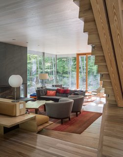 It Took a Whole Family to Build This House - Photo 10 of 13 - One-inch-thick slate clads the fireplace in the living room, which opens to a terrace. The reclaimed coffee table is by Scott Chambers.