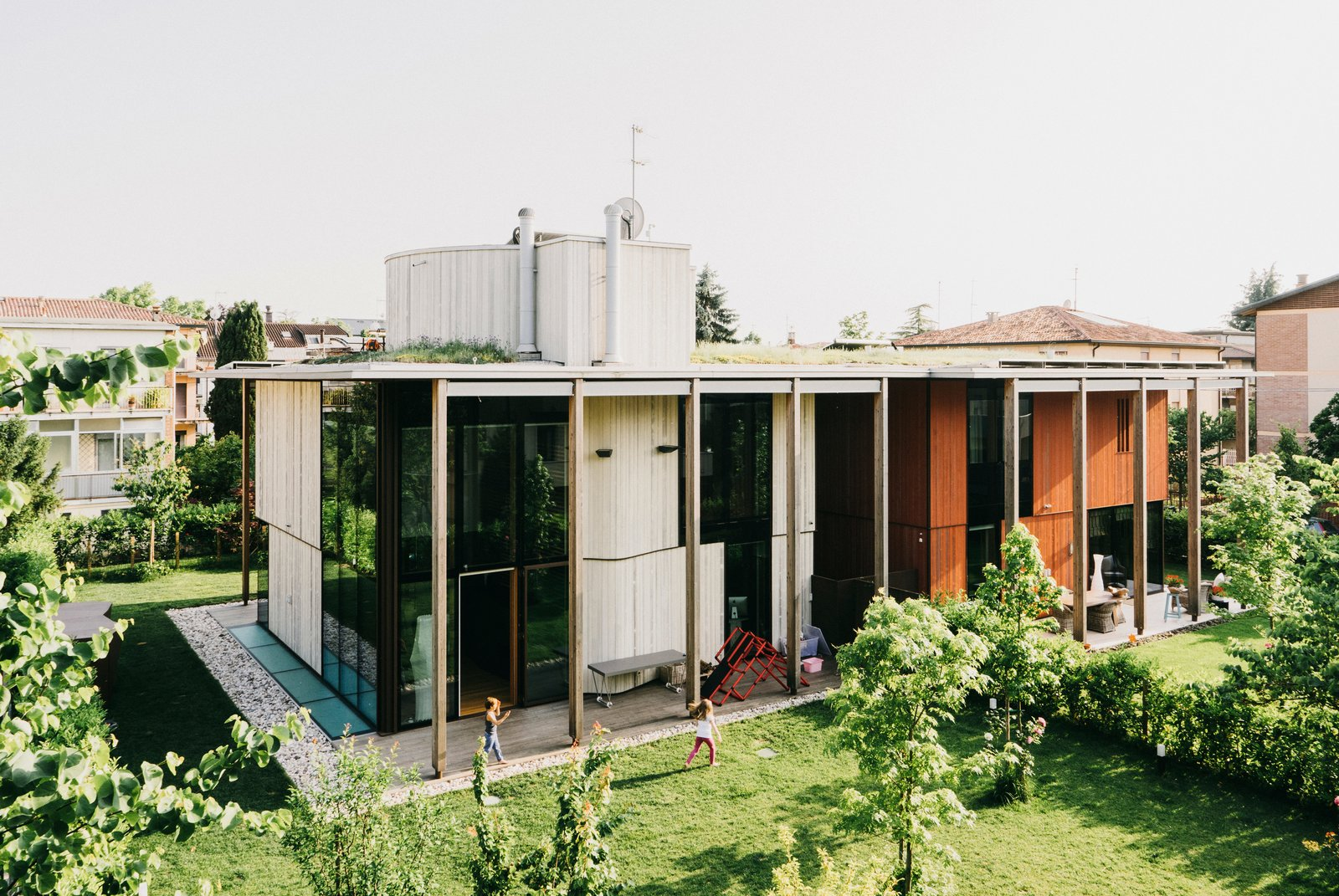 Studiopietropoli created two houses on one site, each with fluid connections to the surrounding garden. A green roof creates a portico between them.