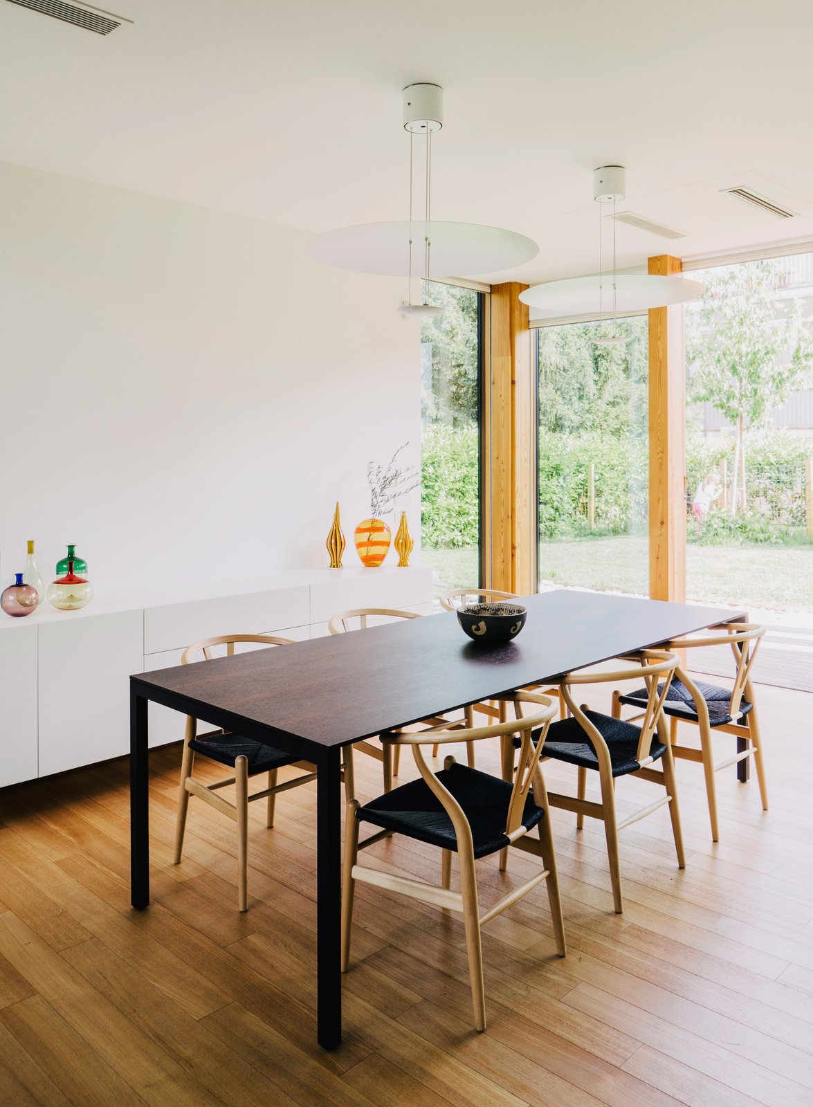 In the dining room, Wishbone chairs by Hans J. Wegner surround a 195 Naan table by Piero Lissoni. Tagged: Dining Room, Table, Storage, Chair, Medium Hardwood Floor, and Pendant Lighting.  Photo 5 of 8 in Could You Share Your Dream Home?