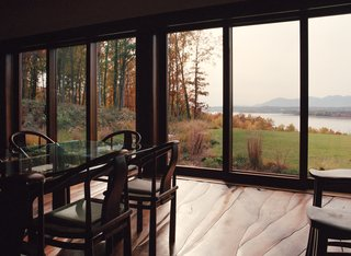 Discover 6 Amazing Riverside Homes - Photo 12 of 12 - The sustainable home features handmade furniture and an undulating floor, all crafted from the site's felled black walnut trees. They lend a craft-oriented feel to the home that's otherwise strictly modern in design and detailing. The waves of the Hudson River are mimicked in the organic, wavy pattern of the walnut flooring.