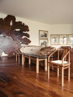 10 Warm Wood Floors - Photo 3 of 10 - The lesson of the ancient redwood—a pillar of its ecosystem for centuries, quickly felled by humans with little understanding of their actions—is an integral part of Shope's new home, built with reclaimed materials and filled with wood furnishings made by his own hand. Carefully crafted, the black walnut floor fits like a jigsaw puzzle.