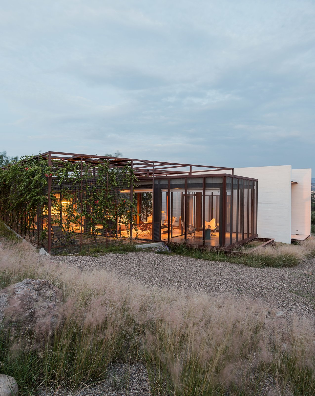 Two art studios adjoin a central volume at this work/live residence built from terracreto (sustainable concrete), glass, and painted steel just outside of San Miguel de Allende, Mexico. Residents Austin and Lida Lowrey, retired design and museum professionals, collaborated with their two daughters—Sheridan, an artist, and Elizabeth, an architect—to design the structure as a place for creative contemplation. Tagged: Exterior, Concrete Siding Material, and House.  Photo 1 of 14 in These Separate Studios Keep a Retired Couple Happy from How to Take a Dwell Photo
