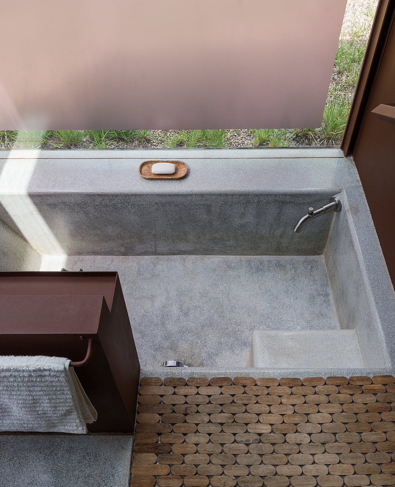 In Lida's studio, terrazzo and granite floors blend seamlessly into a sunken bath, paired with a steel storage unit and a wooden Moroccan bath mat from  Insh'ala, a local antique store. Tagged: Bath Room and Terrazzo Floor.  Photo 12 of 14 in These Separate Studios Keep a Retired Couple Happy