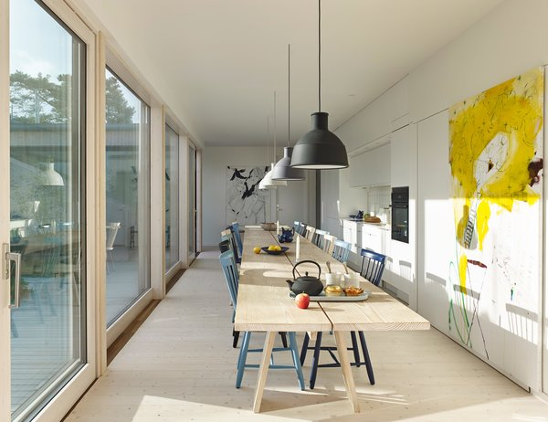 A custom table designed by Staffan Holm, capable of seating 26, runs the length of Anders Bergström and Kristina Lagercrantz's kitchen in Gothenburg. Unfold pendants by Form Us With Love for Muuto, Lilla Åland chairs by Carl Malmsten for Stolab, and a painting by Hampus Pettersson complete the space.