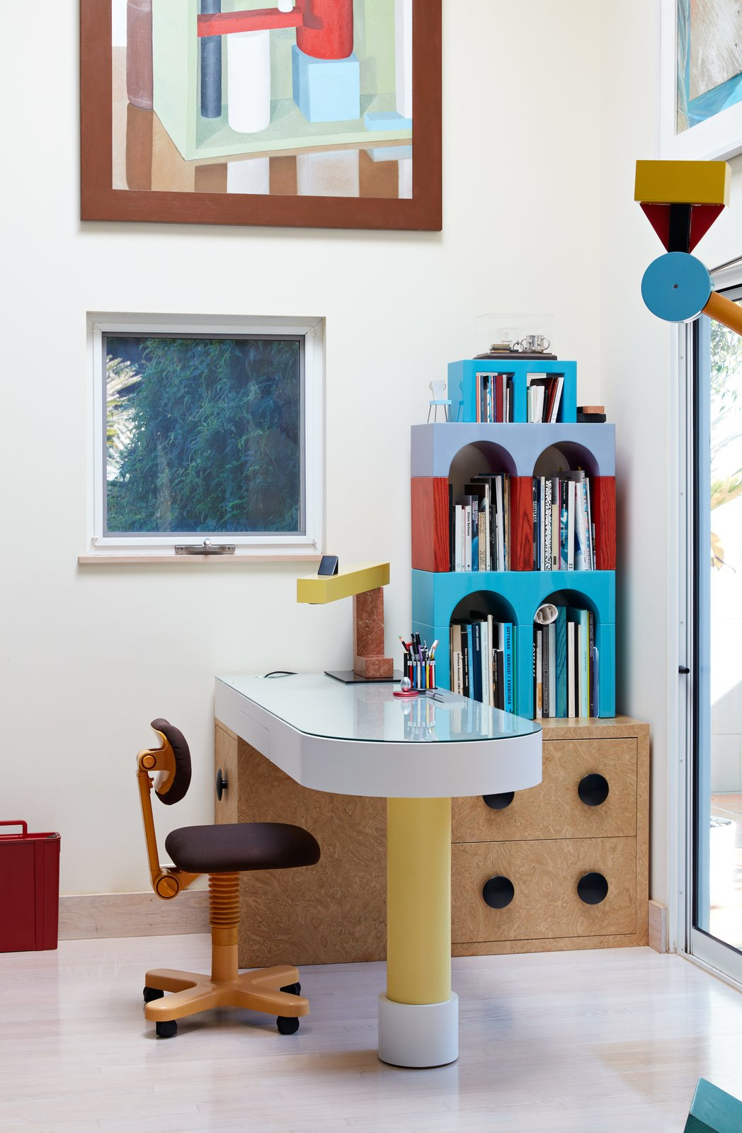 Giotto shelves, a Treetops floor lamp, and an Olivetti chair, all by Sottsass, furnish the home office. Adrian designed the desk, and the painting is by Nathalie Du Pasquier, one of the original Memphis designers. Tagged: Office, Study, Storage, Chair, and Desk.  Photo 6 of 14 in Thank Sottsass for the Most Memphis House Imaginable