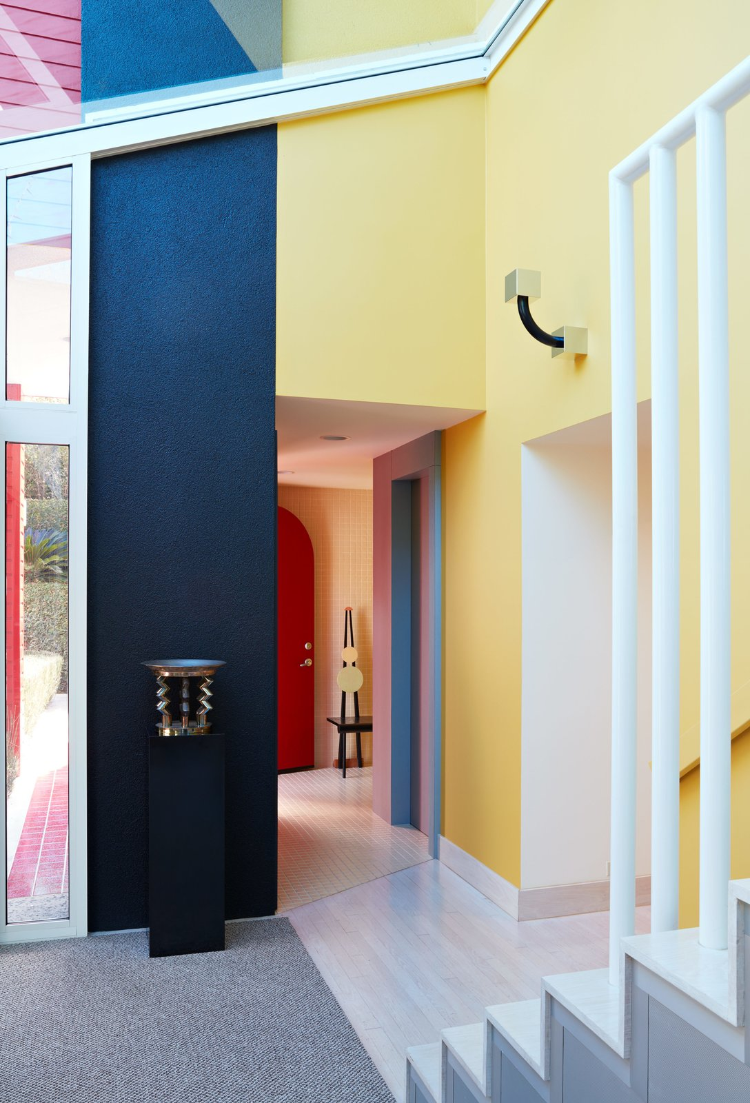 Vignettes of contrasting colors, materials, and shapes frame every corner. A one-of-a-kind chair by Peter Shire sits in the hallway; near the sculptural staircase is a sconce for Yamagiwa and a sterling silver centerpiece for Memphis, both by Sottsass.  Photo 12 of 14 in Thank Sottsass for the Most Memphis House Imaginable