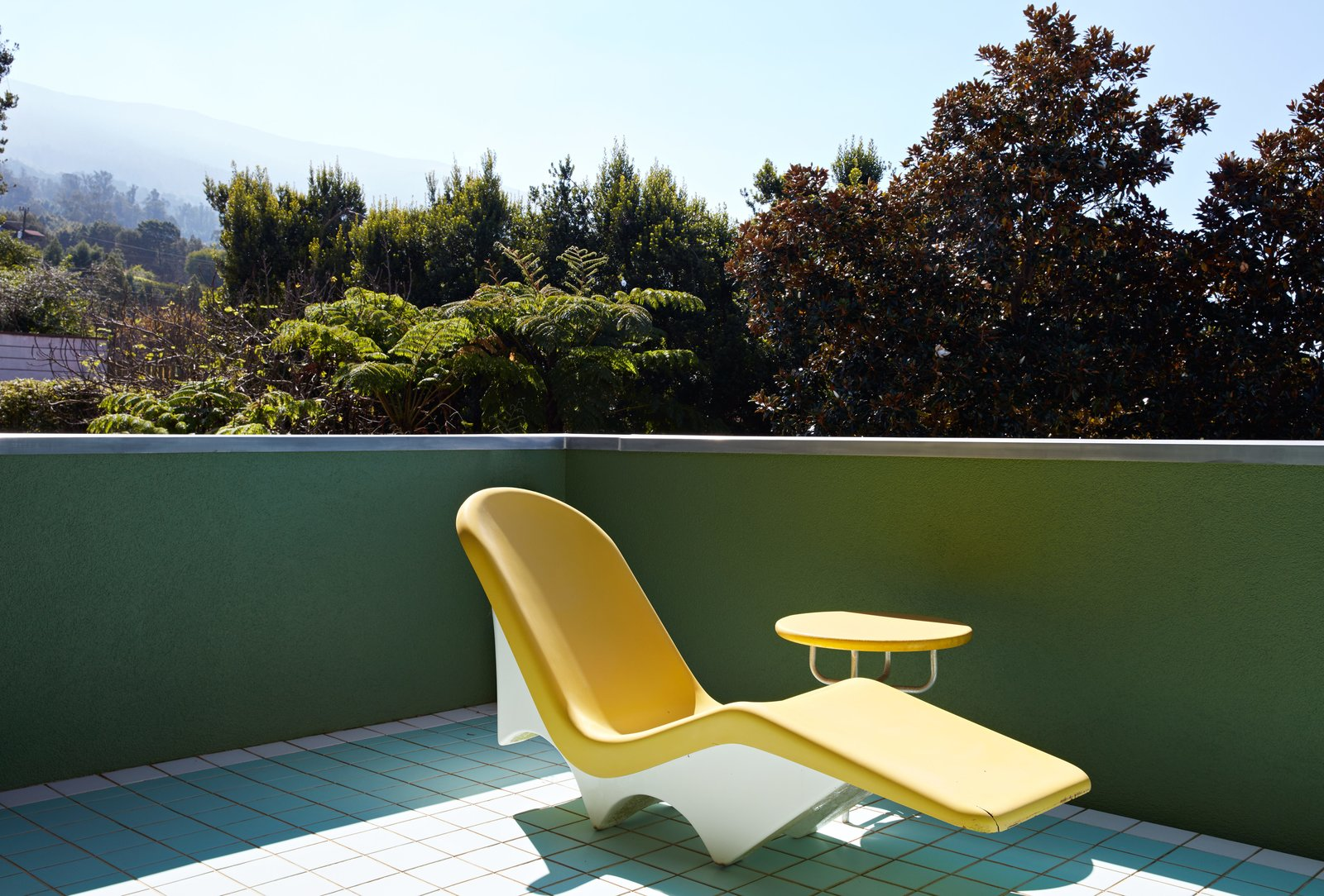 A vintage chaise lounge on the upper floor patio is one of few unnamed designs to be found throughout the residence. Tagged: Outdoor, Small Patio, Porch, Deck, and Tile Patio, Porch, Deck.  Photo 14 of 14 in Thank Sottsass for the Most Memphis House Imaginable