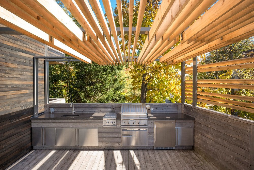 At one end of the L-shaped terrace, Brisson included room for a full outdoor kitchen so the family could prepare meals without stepping inside during the warmer months.  Outdoor by Mike from An Interior Designer Does the Great Outdoors