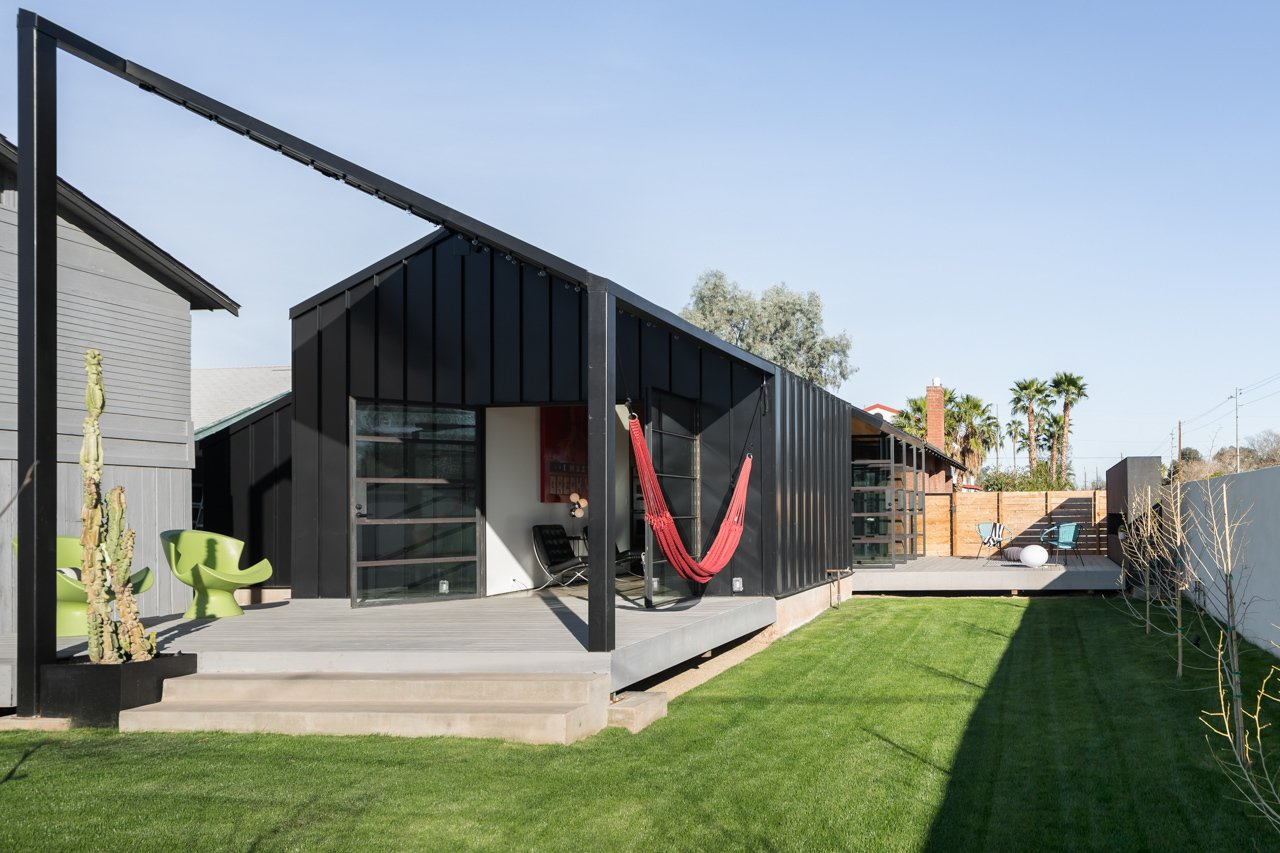 """The modern addition sits on a concrete platform that extends past the house's envelope, creating welcoming patios on each side. """"From any space within the home you are no more than a few steps from one of the outdoor spaces,"""" Busick says. On the west-facing back porch, Green Kite Chairs by Karim Rashid and a poppy-red hammock offer ideal spots from which to take in the sunset."""