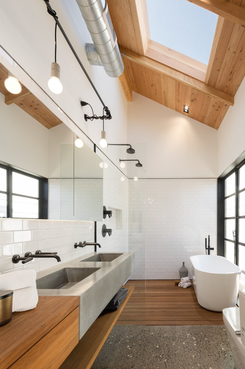 A skylight illuminates the neutral master bathroom, letting bathers contemplate the clouds. The faucets and tub are by Brizo, and the sinks are SlabHaus.  Bathroom by Ellen Gray from Amazing House is Half Historic and Half Modern