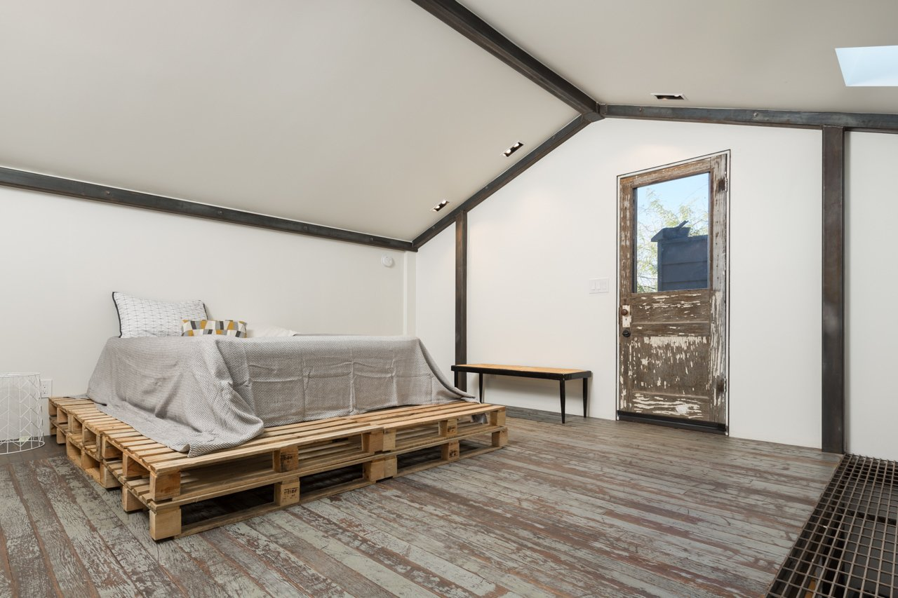 An additional aspect of the renovation was the conversion of a dilapidated carriage house into a sleek, two-story studio that flanks the rear porch. A structural steel frame inside reinforces the structure while recalling the main house's steel cladding.  Bedrooms by Dwell from Amazing House is Half Historic and Half Modern
