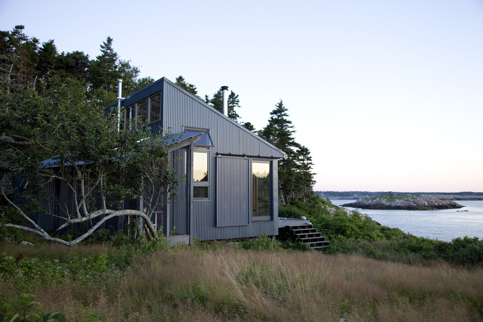This quaint cabin is located on Ragged Island, 20 miles off the coast of Maine. Photo by: Eirik Johnson Tagged: Exterior, House, Metal Siding Material, Cabin Building Type, and Shed RoofLine.  Photo 73 of 101 in 101 Best Modern Cabins from Modern, Off-the-Grid Homes