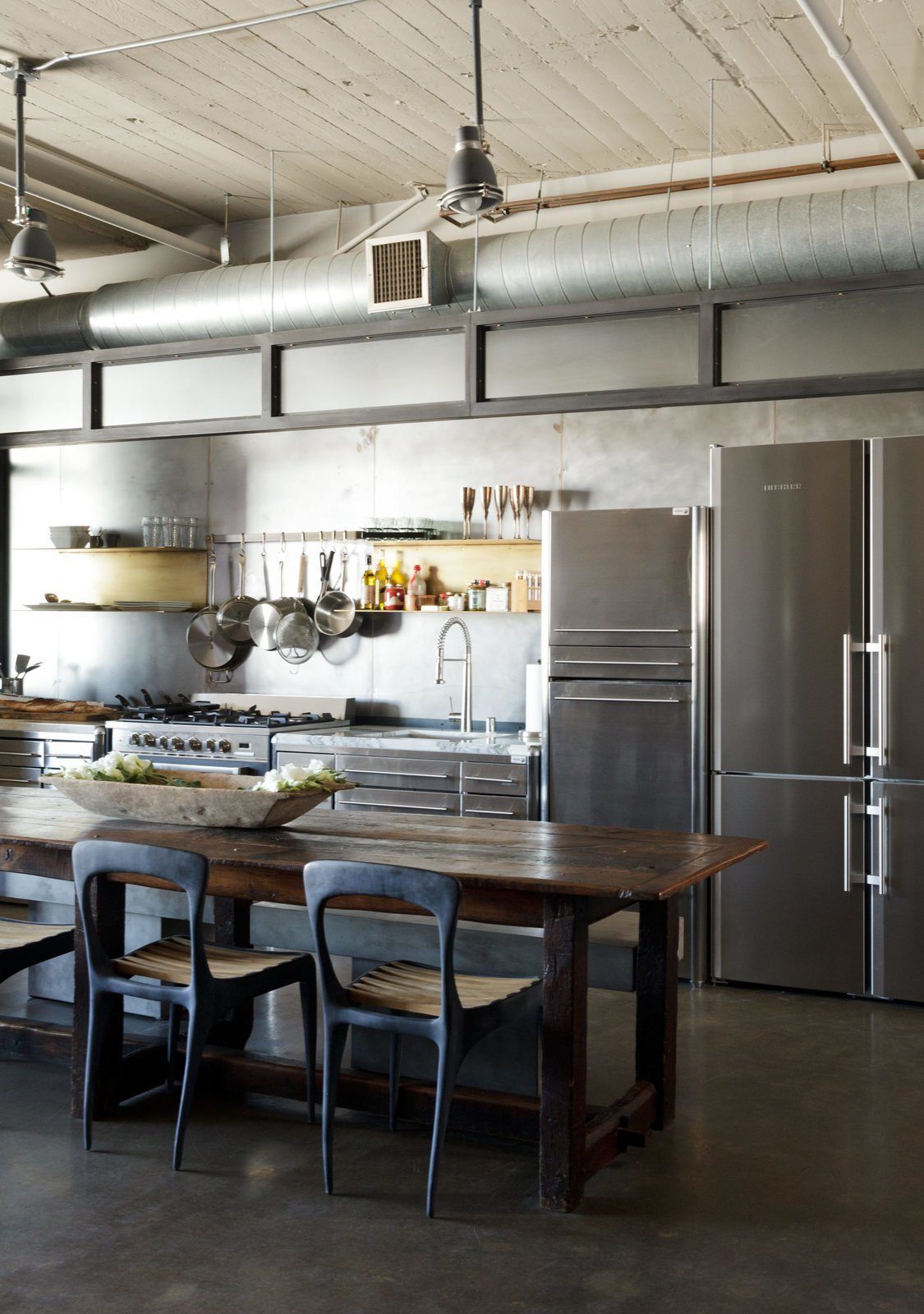 In a loft renovated by designer Andrea Michaelson, a Liebherr refrigerator blends in with stainless-steel cabinets from Fagor. Flow chairs by Henry Hall Designs and CB2 benches pull up to an antique farm table.  Photo 2 of 6 in Steel and Brass Cover Nearly Every Surface of this Industrial L.A. Kitchen