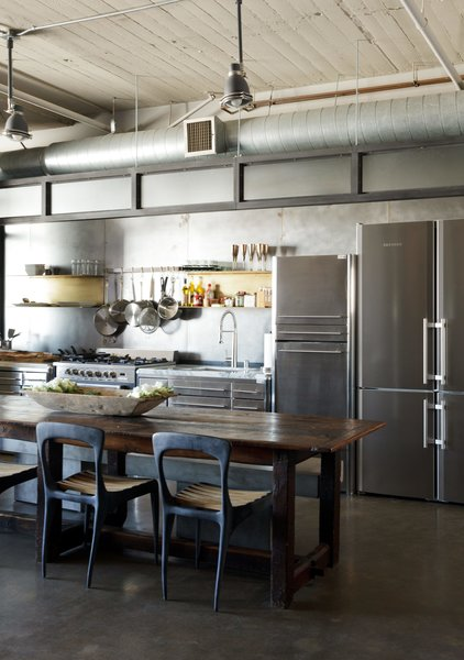 In a loft renovated by designer Andrea Michaelson, a Liebherr refrigerator blends in with stainless-steel cabinets from Fagor. Flow chairs by Henry Hall Designs and CB2 benches pull up to an antique farm table.