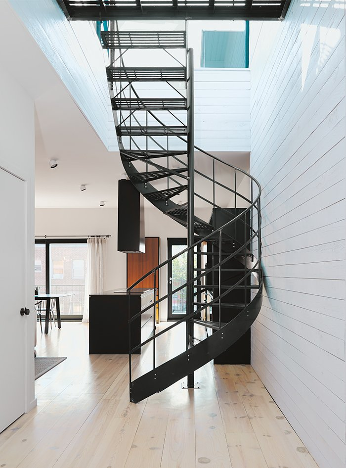 Di Ioia and Bédard designed the wrought-iron spiral staircase that leads to the rooftop terrace and sauna as a visual nod to Montreal's signature outdoor stairways. Tagged: Staircase, Metal Tread, and Metal Railing.  Scandinavian by Sikhumbuzo Mbatha from Scandinavian Style Revives This Montreal Home