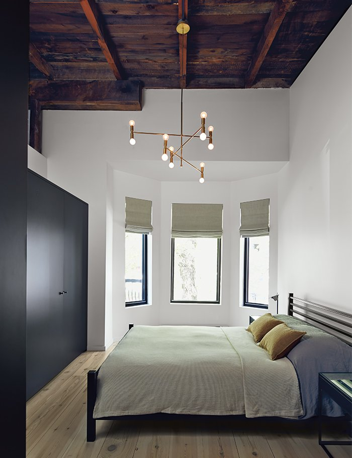 The master bedroom includes an armoire by Kastella and a chandelier by Lambert & Fils. A portion of the ceiling was pared back to expose the underside of the original roof. Tagged: Bedroom, Bed, Night Stands, Pendant Lighting, and Light Hardwood Floor.  Photo 9 of 14 in Scandinavian Style Revives This Montreal Home
